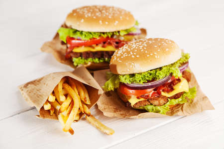comida chatarra: Deliciosa hamburguesa y papas fritas en fondo de madera