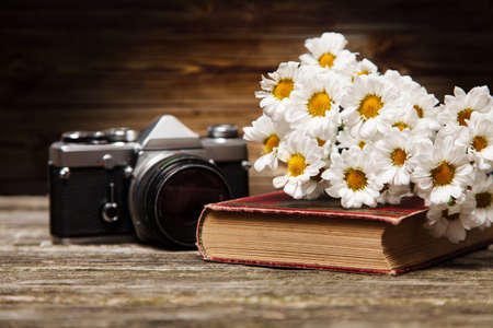 Photo camera, daisies and a book on a wooden background photo