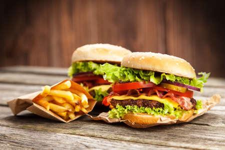 comida chatarra: Deliciosa hamburguesa y papas fritas en el fondo de madera