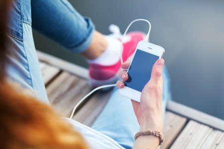 adolescente: Joven mujer sentada en el muelle de la celebración de un teléfono inteligente. Foto de archivo