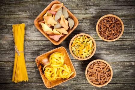 pastas: Diferentes tipos de pasta sobre fondo de madera