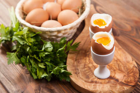 eggcup: Boiled eggs on a wooden background.