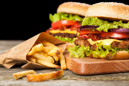 hamburger: Delicious hamburger and french fries on wooden background