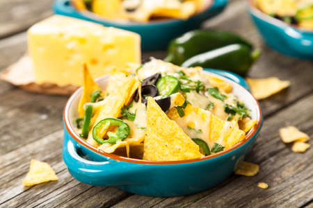 nachos: Nachos with melted cheese and salsa, guacamole and cheese dips
