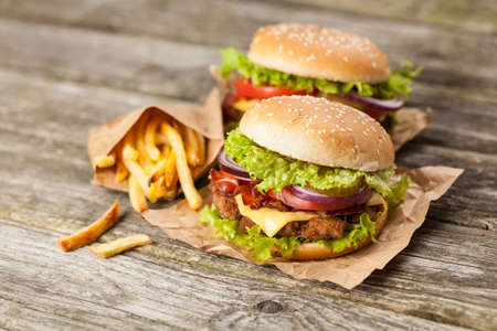 hamburger and fries: Delicious hamburger and french fries on wooden background