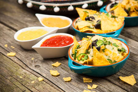 melted cheese: Nachos with melted cheese and salsa, guacamole and cheese dips