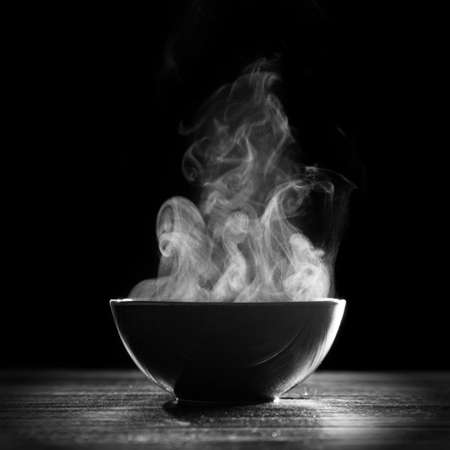 smoke: Bowl of hot soup on black background