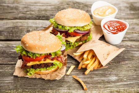 おいしいハンバーガーとフライド ポテトの木製の背景