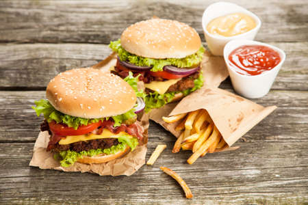 gourmet burger: Delicious hamburger and french fries on wooden background