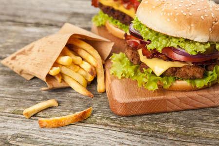 onion: Deliciosa hamburguesa y papas fritas en el fondo de madera