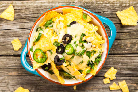 chips and salsa: Nachos with melted cheese and salsa, guacamole and cheese dips