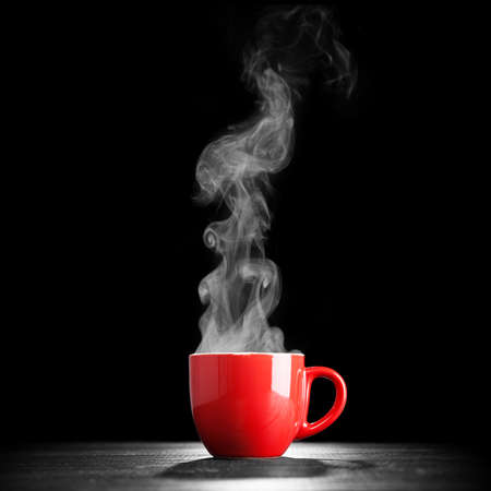 暗い背景の上にコーヒー カップを蒸し