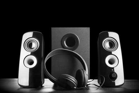 Moderne zwarte luidsprekers en een koptelefoon op donkere achtergrond Stockfoto