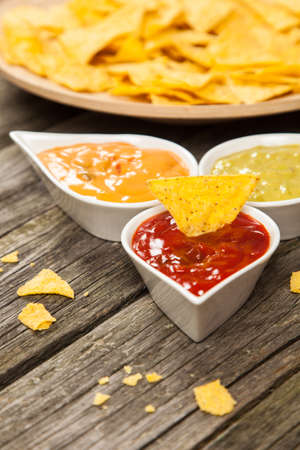 nacho chip: Plate of nachos with salsa, cheese and guacamole dips Stock Photo