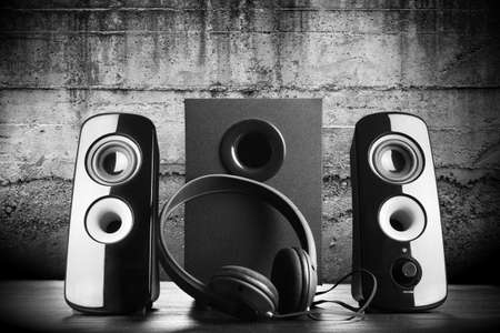 Modern black sound speakers and headphones on dark background