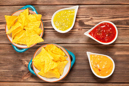 salsa: Plate of nachos with salsa, cheese and guacamole dips Stock Photo