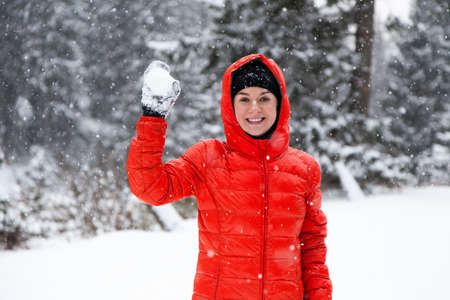 snowballs: Pretty young woman playing snowballs in the mountains Archivio Fotografico