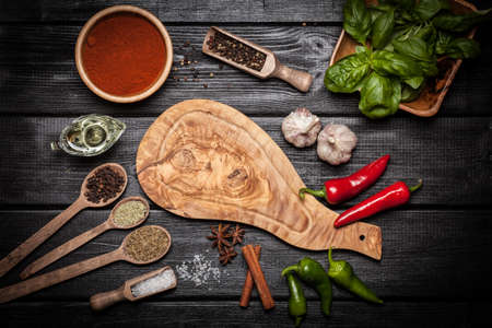 black board: Olive wood board with different spices on wooden surface