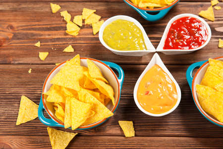 nachos: Plate of nachos with salsa, cheese and guacamole dips Stock Photo