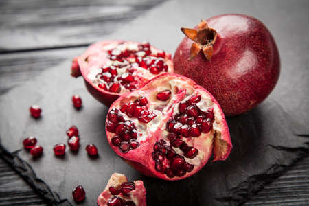 Red juice pomegranate on dark background