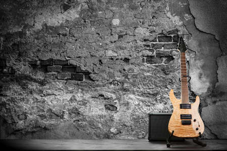 amp: Electric guitar on a brick wall background.