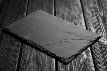Black slateboard on dark wood background