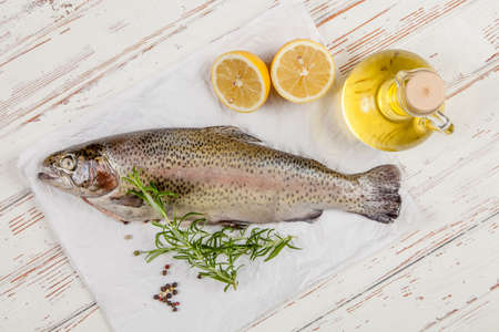 speckled wood: Fresh whole trout on white wood Stock Photo