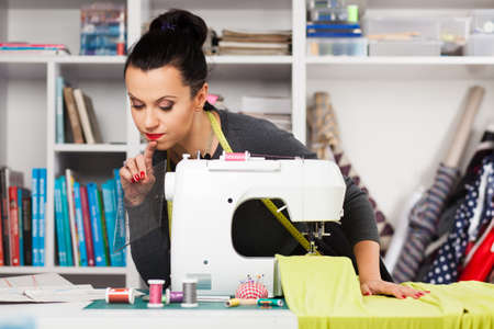attractive  female: Young woman working with a sewing machine