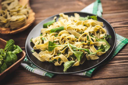 grated parmesan cheese: Cooked tagliatelle pasta with greens and grated parmesan cheese Stock Photo
