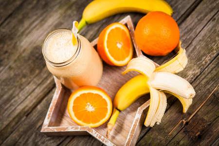 milkshake: Banana orange milkshake on wooden table