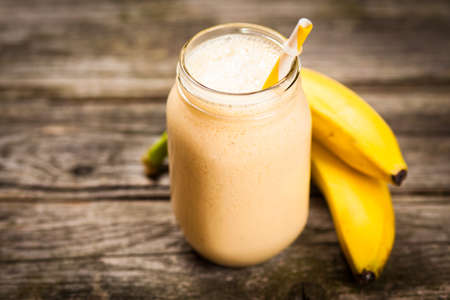 Banana milkshake on wooden table 免版税图像