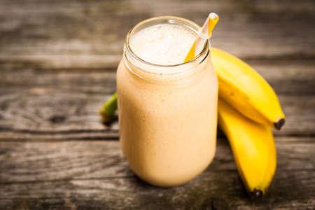 Banana milkshake on wooden table Foto de archivo
