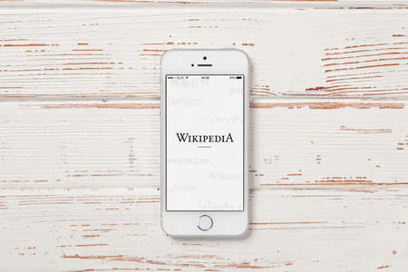 wikipedia: WROCLAW, POLAND - APRIL 12, 2016: Apple iPhone SE smartphone with Wikipedia app on screen