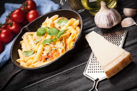 Traditional penne pasta in cast iron skillet Stock Photo