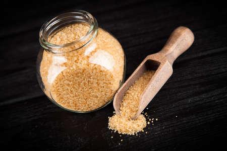 Brown unrefined sugar on black backound