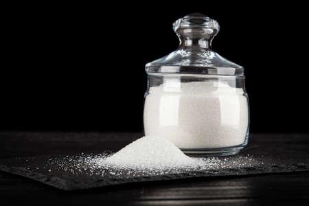 refined: White refined sugar on black backound