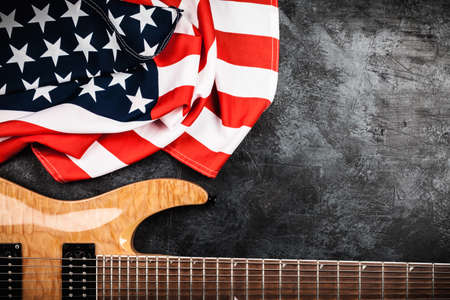 Electric guitar and USA flag on grey background