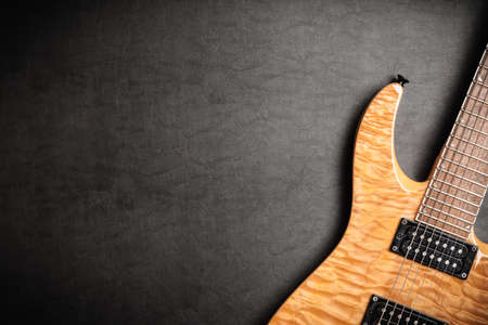 top 7: Electric guitar with natural wood finish on dark leatherbackground