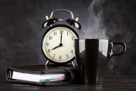 job deadline: Alarm clock and a cup of coffee on dark background