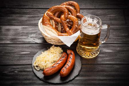 Traditional german food of pretzels, sauerkraut, bratwurst and beer on wooden table