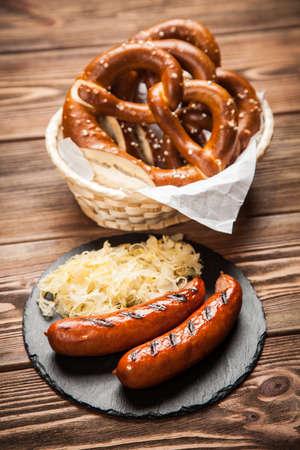 comida alemana: Traditional german food of pretzels, sauerkraut and bratwurst on wooden table Foto de archivo