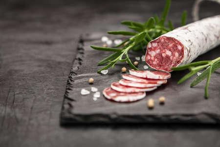 Traditional italian salami on dark background