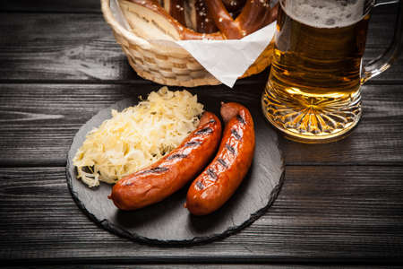 german food: Traditional german food of pretzels, sauerkraut, bratwurst and beer on wooden table