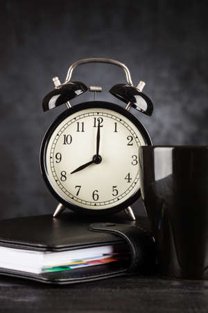 todo list: Alarm clock and a cup of coffee on dark background