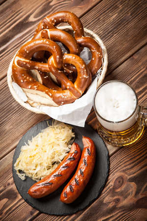comida alemana: Traditional german food of pretzels, sauerkraut, bratwurst and beer on wooden table