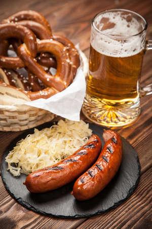comida alemana: alemana de la comida tradicional de pretzels, chucrut, salchichas y cerveza en mesa de madera