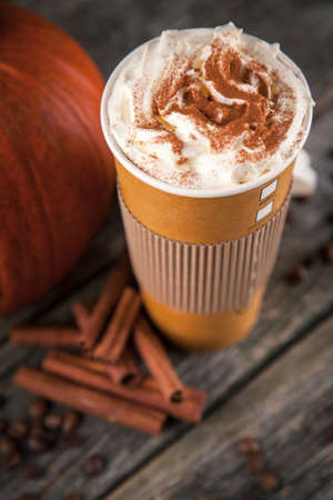 Pumpkin spice latte in a paper cup on dark background Фото со стока