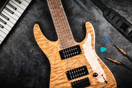top 7: Electric guitar with natural wood finish on grey background Stock Photo