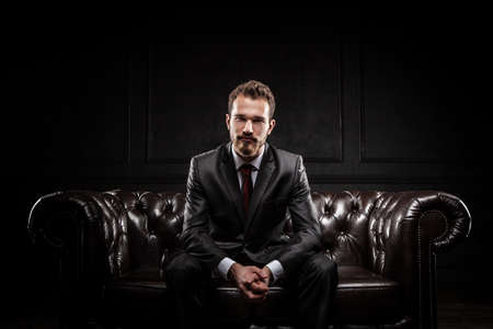 red sofa: Young confident businessman in a suit Stock Photo
