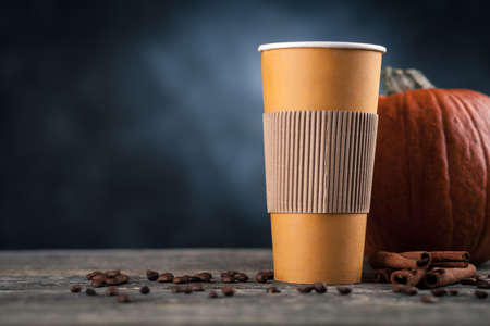 Pumpkin spice latte in a paper cup on dark background Stock Photo